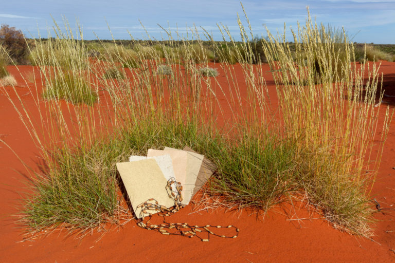 Curtin Springs Paper laid out on the red sand with pieces of artisan jewllery made from the paper